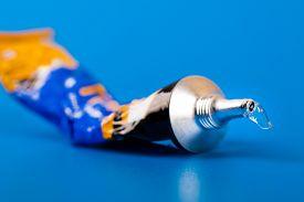Closeup Of  Super Glue Tube On Blue Background