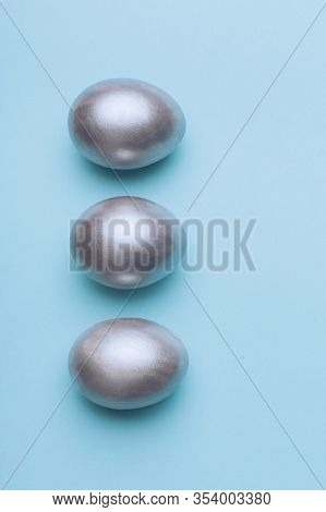 Silver Metal Easter Eggs On A Blue Background, Decoration, Holiday Background Concept. Pastel Tone,