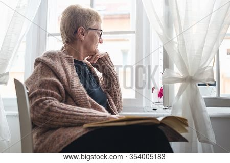 Senior Woman Relaxing At Home. Woman Relaxing On Window At Home. Hipster Lifestyle. Senior Woman At