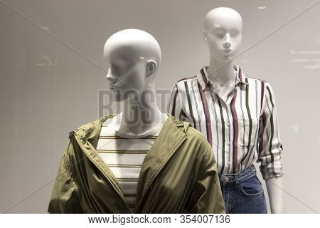 Two Bald Female Mannequins Are Dressed In A Striped Shirt, Green Khaki Jacket, Windbreaker, Jeans. Y