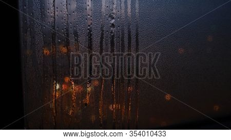 Close-up Of Window With Raindrops On Blurred Background Of Lights. Concept. Dim Lights Shine Through