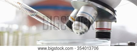 Scientist Dosing A Drop With Pipet To Exam With Microscope Closeup