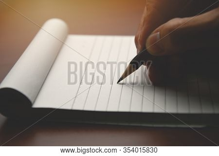 Male Hand With Pencil Writing On Notebook. Male Working In Home Office