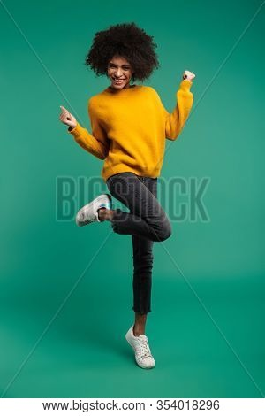 Full length portrait of a smiling young african woman wearing sweater jumping isolated over green background, celebrating success