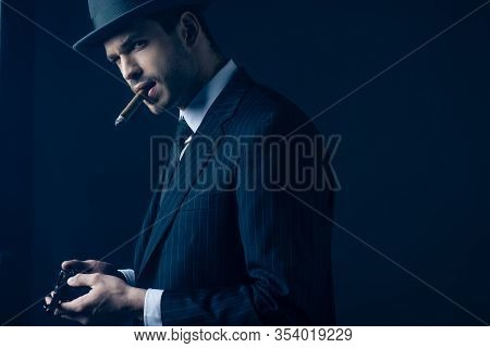 Gangster With Cigar In Mouth Loading Gun On Dark Blue Background