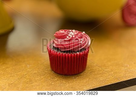 Top View Of Delicious Chocolate Cupcake With Red Cream Icing And Sprinkles. Cupcake With Colorful Ch