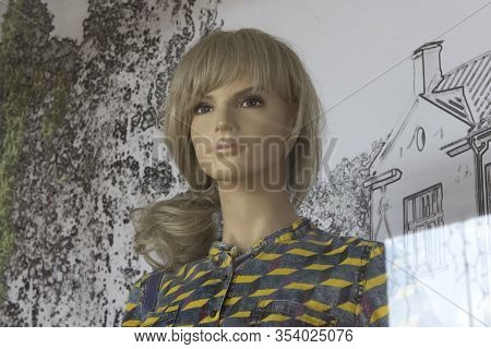 Female Mannequin With Long Blond Hair In A Shirt Or Dress. Human-like Mannequin With Expressive Eyes