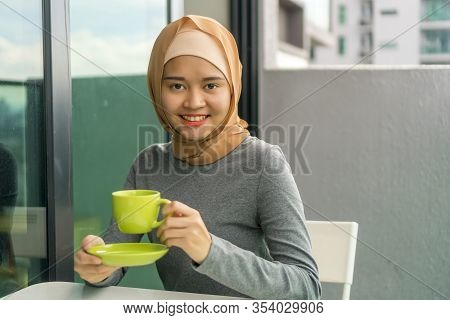 Portraiture Of Cute Malay Muslim Wearing Hijab Outdoor Holding Coffee Cup