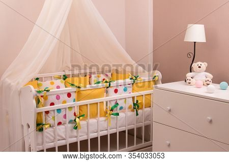 Crib In A Four-poster Room. Crib With Colored Bedding. Crib With Soft Sides Of Pillows.