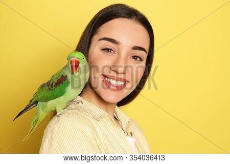 Young Woman With Alexandrine Parakeet On Yellow Background. Cute Pet
