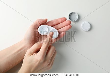 Woman Takes Contact Lens From Case On White Background, Top View