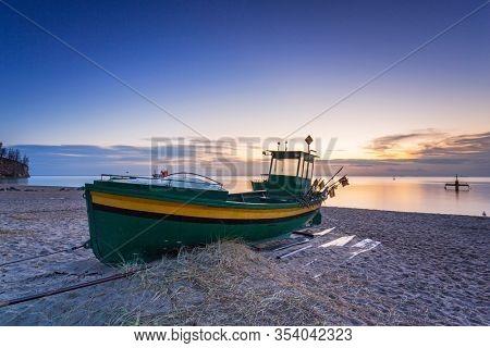 Fishing boat near the Baltic Sea at sunrise in Gdynia Orlowo, Poland