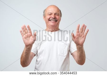 Bald Man Shows Ten Fingers And Laughs Joyfully Isolated On A White Background