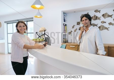 Smiling Happy Woman Guest In The Lobby Interior Of The Resort Spa Hotel, Male Receptionist Working N