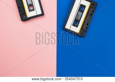 Two Retro Audio Cassettes Flat Lay On Colorful Blue And Pink Background Top View With Copy Space. Cr