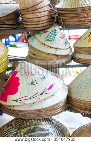 Handmade traditional Vietnamese leaf hats for sale in a market Hoi An, Vietnam, Asia, decorated with the wording Viet Nam in English and Vietnamese