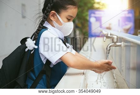 Asian Student  Washing Hands At The Outdoor Wash Basin In The School. Preventing Contagious Diseases