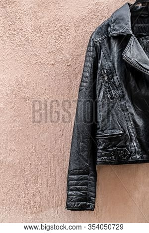 Black Leather Jacket On Pink Wall With Copy Space.