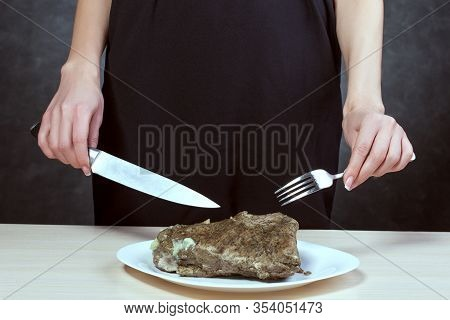 Woman With Beautiful Hands Holds A Fork And Knife. In Front Of Her Is A Plate With A Piece Of Meat.