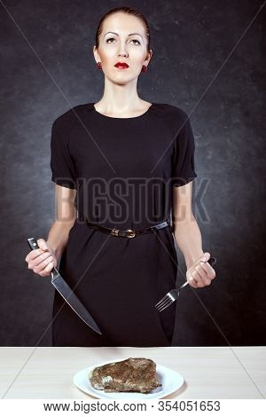 Young Beautiful Woman Holding A Knife And A Fork In Her Hands. In Front Of Her Is A Plate With A Pie