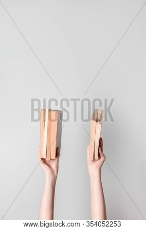 Female Hands Holding Books, On Neutral Background With Copy Space.