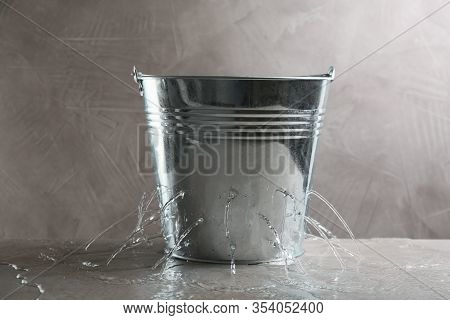 Leaky Bucket With Water On Table Against Grey Background