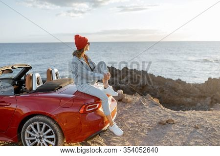 Woman Enjoying Beautiful View On The Ocean, Sitting On The Convertible Car On The Rocky Coast During