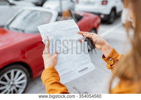 Woman Holding A Lease Agreement At The Car Parking With Beautiful Red Car On The Background, Close-u