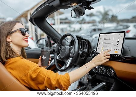 Cheerful Woman Controlling Car With A Digital Dashboard, Switching Autopilot Mode While Driving A Ca