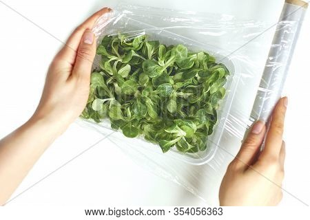 Woman Using Food Film For Food Storage On A White Table. Roll Of Transparent Polyethylene Food Film