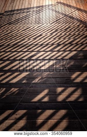 Staircase With A Shadow From The Railing. Close-up Of Descending Down The Staircase With Wooden Step