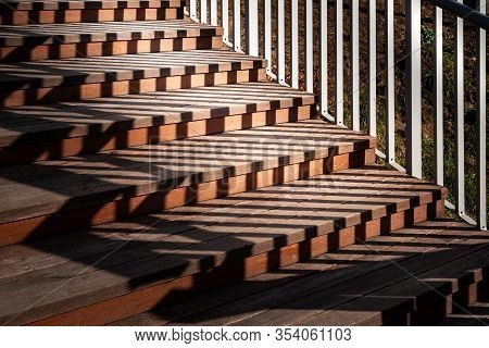 Staircase With A Shadow From The Railing. A Staircase Descending With Wooden Steps And Metal Railing