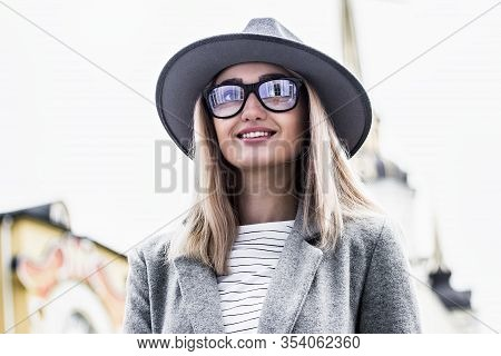 Portrait Stylish Young Woman In Hat And Eyeglasses Looking Away And Smiling While Standing Outdoors.