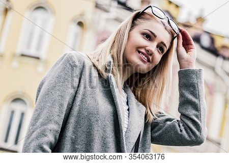 Happy Young Woman In Urban Outfit Holding Eyeglasses In Hand On Her Head While Standing On City Stre