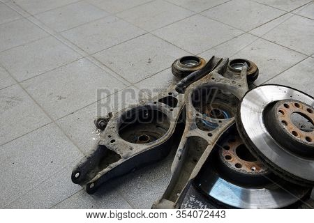 Old Worn Out Spare Parts Remained After Car Repair Lie On The Floor Of A Car Repair Shop. Service, R