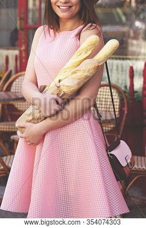 Fresh Baguettes. Closeup Of Beautiful Young Smiling Woman In Pink Dress And Hat Holding Baguettes Wh