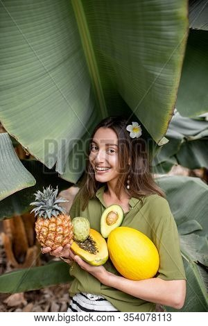 Portrait Of A Young Smiling Woman With Exotic Food In Banana Leaves, Holding Ananas, Papaya, Melon,