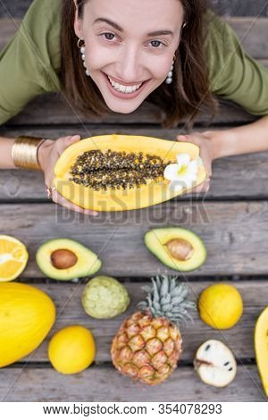 Young Woman With Exotic Fruits And Berries On The Table, View From Above. Ananas, Papaya, Melon, Avo
