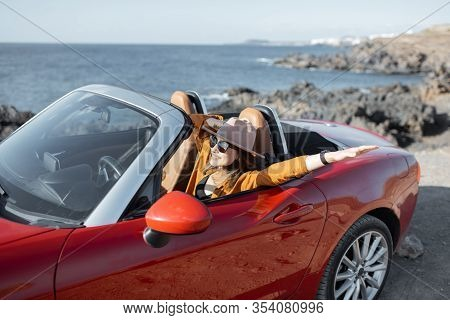Young Stylish Woman In Hat Driving Convertible Car Near The Ocean, Enjoying Summer Vacations While T