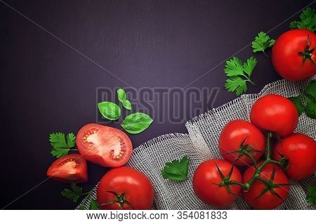 Red Tomato And Basil  On A Dark Background.. Top View. Composition From Tomato And Fresh Herb. Sprin