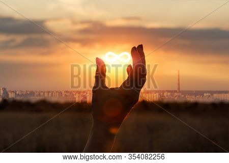 Concept Of Unlimited Internet. Hand Shows The Sign Of Infinity In The Sun.