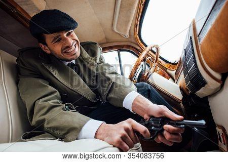 Low Angle View Of Tense Mafioso With Gun In Ambush Sitting In Car