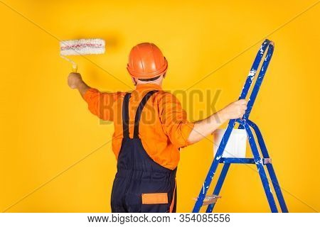 Foreman Inspector. Senior Man Painter Use Roller On Ladder. Painting The Wall In Yellow. Professiona