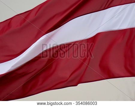 Latvian Flag Waving In Strong Wind On 18th November Day, Lots Of Motion Blur