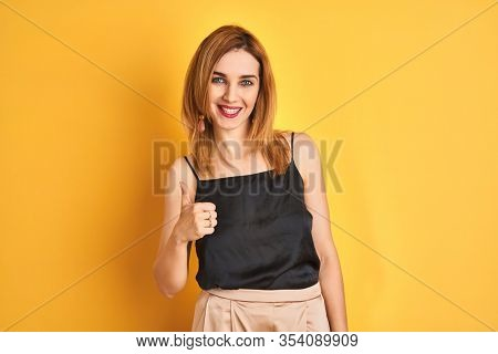 Redhead caucasian business woman standing over yellow isolated background doing happy thumbs up gesture with hand. Approving expression looking at the camera with showing success.
