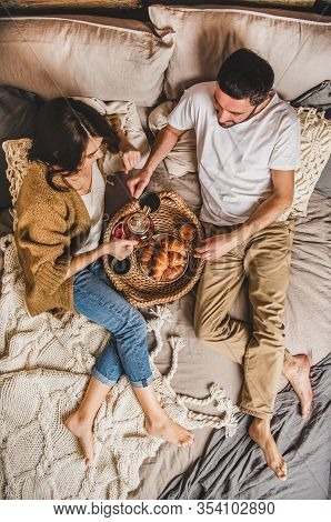 Young Happy Couple Lying In Bed Barefoot And Having Breakfast