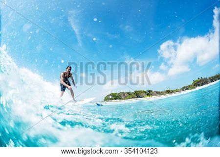 HURAA , MALDIVES MARCH 10, 2019: Hispanic young man surfs the wave on the Sultans surf spot in Maldives