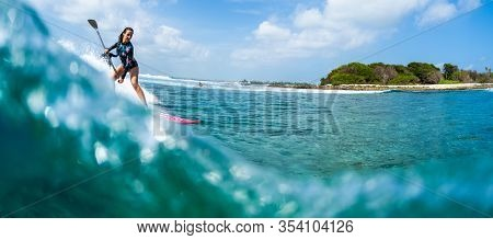HURAA , MALDIVES MARCH 10, 2019: Young woman surfs the wave on the Sultans surf spot in Maldives