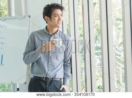 A 25-35 Year Old Asian Man Smiled Happily And Relaxed In A White Office. He Held A Coffee Cup And Lo
