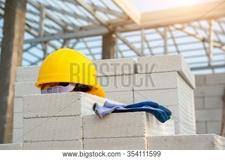 Yellow Hard Hat On At Construction Site,hard Hat And Glove Construction Concepts.